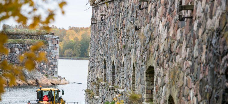 Kuvassa näkyy Suomenlinnan muuria ja keltainen traktori