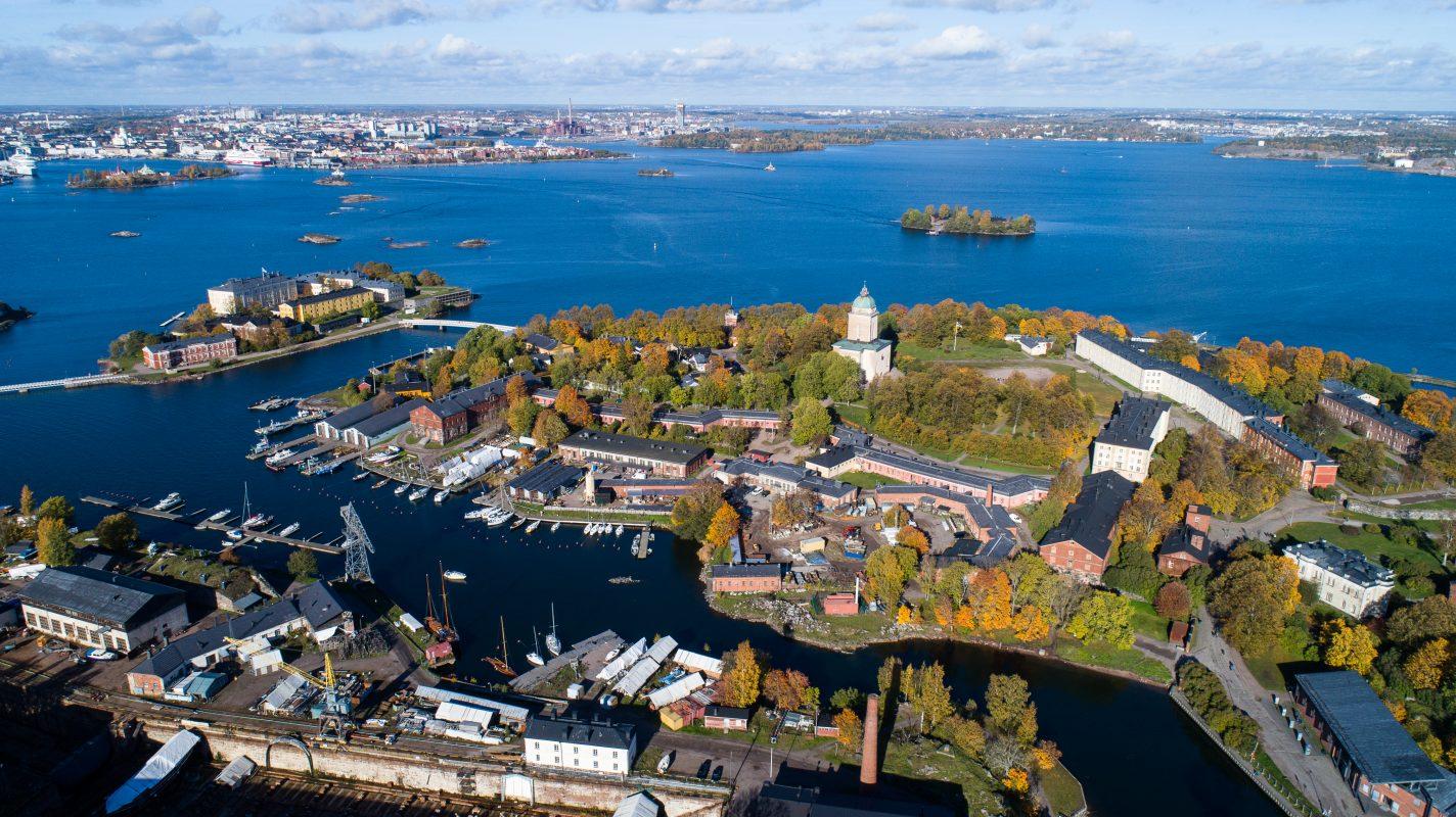 Ilmakuva Suomenlinnasta syksyllä. Kuvassa taustalla Helsinki