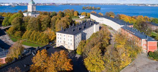 Syksyinen ilmakuva Suomenlinnasta, jossa näkyy Isomustasaari asuinrakennuksineen sekä kirkko ja merimaisema