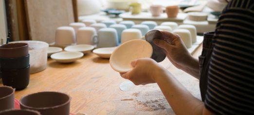 Kädet, jotka hiovat keramiikka-astiaa valmiiksi.