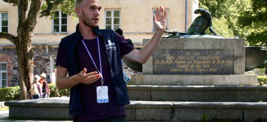 Opas seisoo linnanpihalla haudan edessä