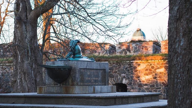 Kuvassa ehrensvärdin hauta keväisessä maisemassa. Taustalla muuria ja Suomenlinnan kirkko