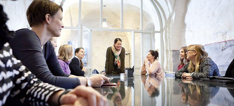 Ihmisisä istumassa kokoustilan pöydän ympärillä