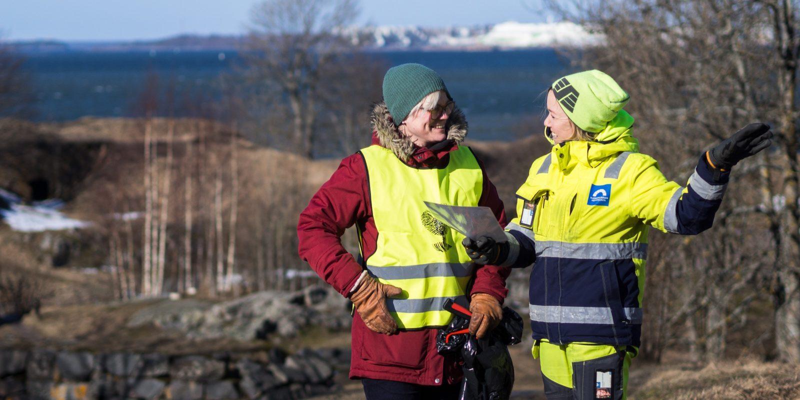 Puistokummiohjaaja opastaa puistokummia , taustalla Suomenlinnan maisemaa.