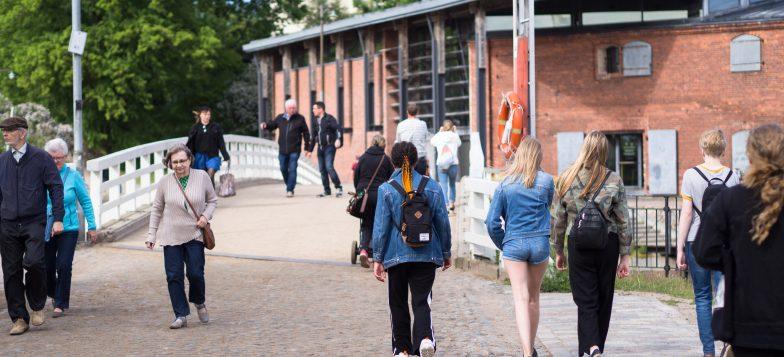 Kuvassa kävijöitä kävelemässä Susisaaren sillalla kesällä