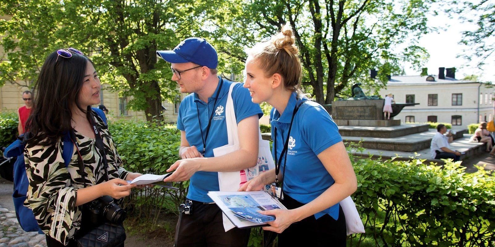 Kuvassa kaksi matkailuneuvojaa opastavat kävijää Suurella linnanpihalla