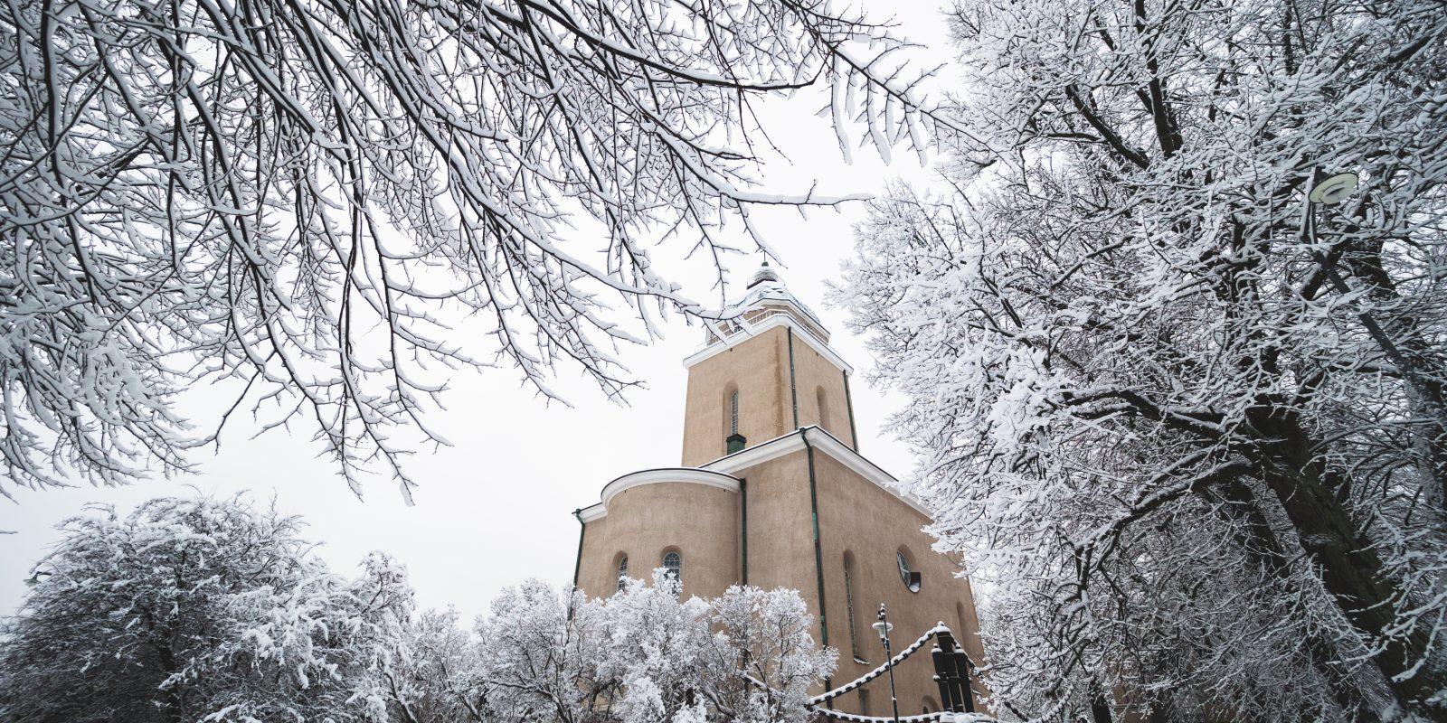 Kuvassa Suomenlinnan kirkko jota kehystää lumiset puiden oksat.
