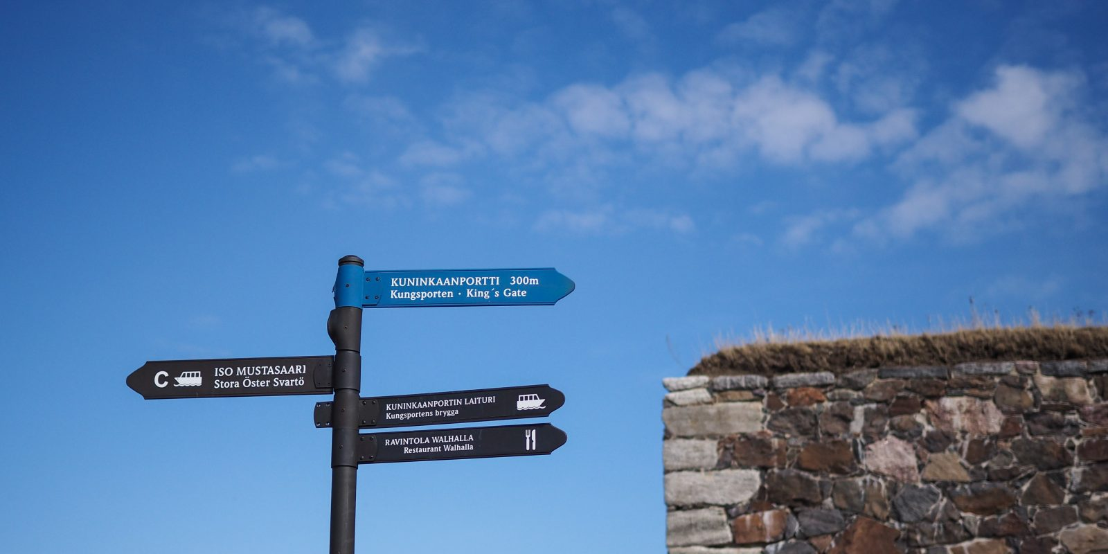 Kuvassa Suomenlinnan opaste, jossa ylin viitta on sininen ja muut viitat mustia. Taustalla sininen taivas ja muuria.