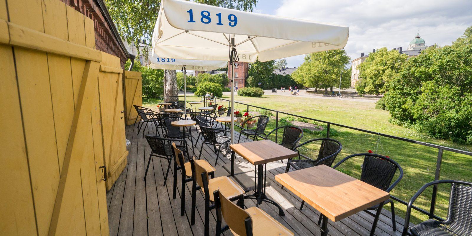Kuvassa Linna baarin terassi, jossa tuoleja, pöytiä ja punaisia kukkia. Taustalla puistoa ja taivasta