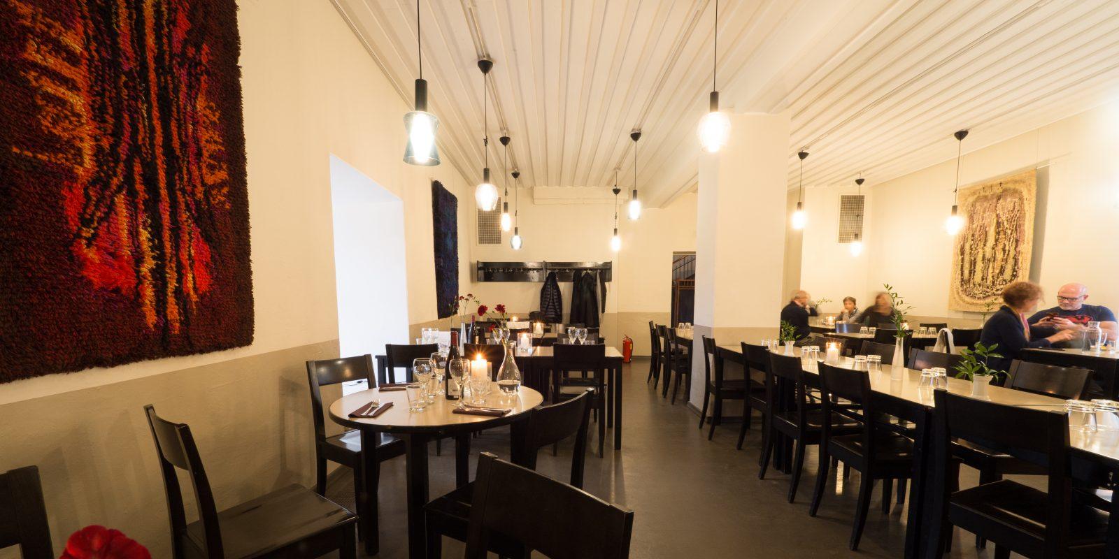 Kuvassa ravintola sisältä tunnelmallisessa valossa. Ihmisä syö pöydän ääressä.