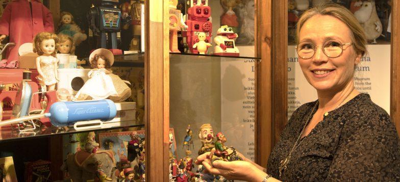 Petra Tandefelt museossaan vitriinin edessä lelu kädessään.