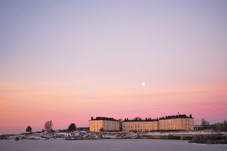 Länsimustasaaren asuinrakennukset auringonnousun aikaan. Kuu loistaa kirkkaana talojen yläpuolella