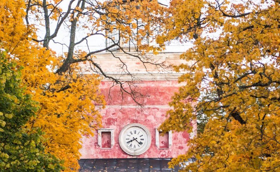 Kuvassa näkyy rantakasarmin vaalenpunainen tornikello ja värikkäät puiden lehdet