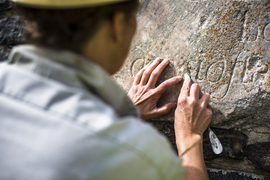 Kuvassa näkyy kädet, jotka kunnostaa kuninkaanportin muistolaatan kaiverrusta