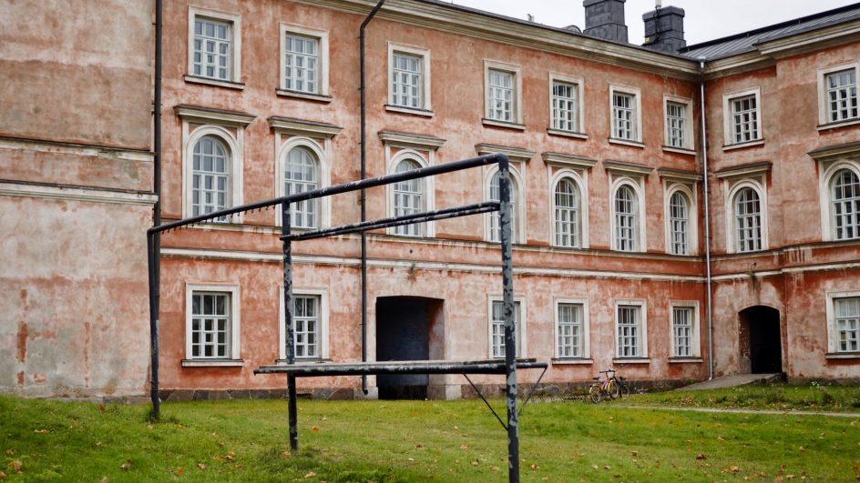 Vaasan kasarmin rakennus, jonka edessä mattojen tamppausteline ja vihreä nurmikko