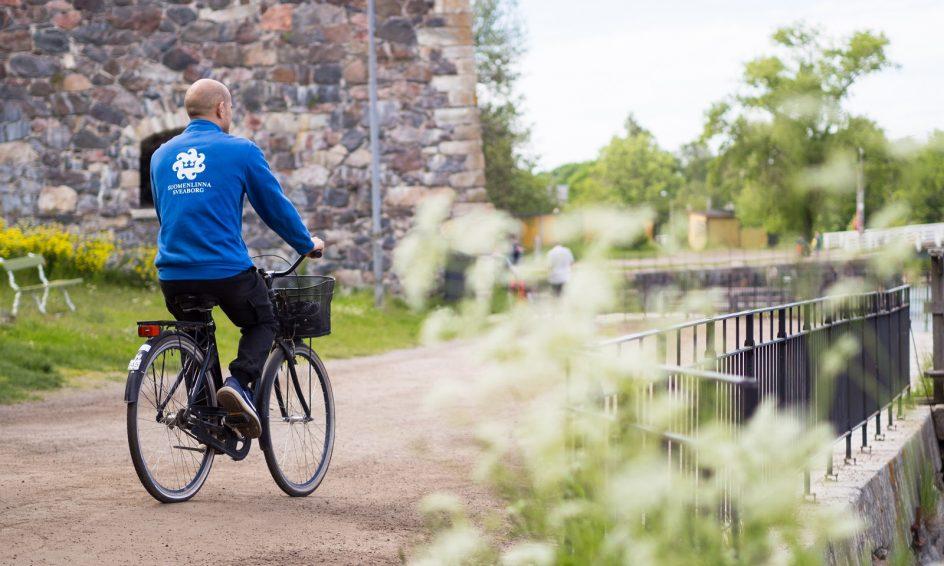 Kuvassa Suomenlinnan kesävalvoja pyöräilee. Hänellä on sininen paita jossa valkoisella teksti suomenlinna ja logo. Taustalla muuria ja etualalla valkoisia kukkia.