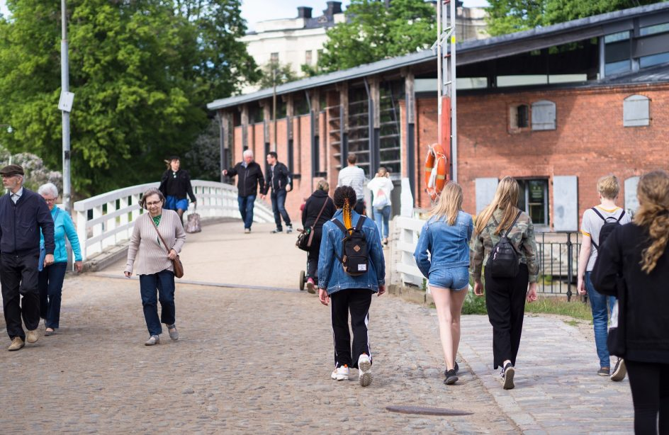 Kuvassa matkailijoita kävelemässä Susisaaren sillalla kesällä