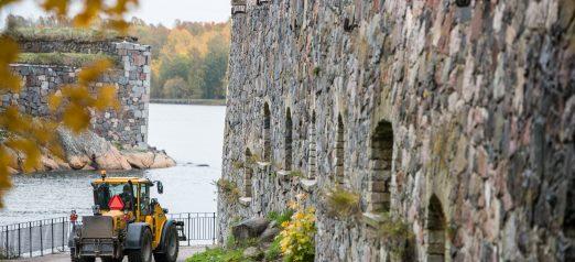 Kuvassa keltainen traktori ajamassa muurin vieressä. Taustalla syksyistä maisemaa