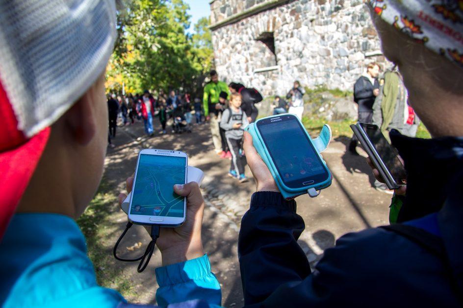 Lapset pelaavat Pokémon Go -puhelinsovellusta Suomenlinnassa.