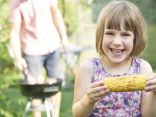 Nuori tyttö syö maissia pihalla hiiligrilin edessä. Kuva liittyy juttuun, jossa käsitellään ruokavalion vaikutuksia syöpään.