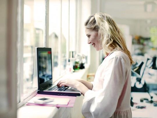 Hymyilevä nainen kannettaansa kanssa tekemässä töitä ikkunalaudalla. Kuva sivustolla Ilman syöpää.