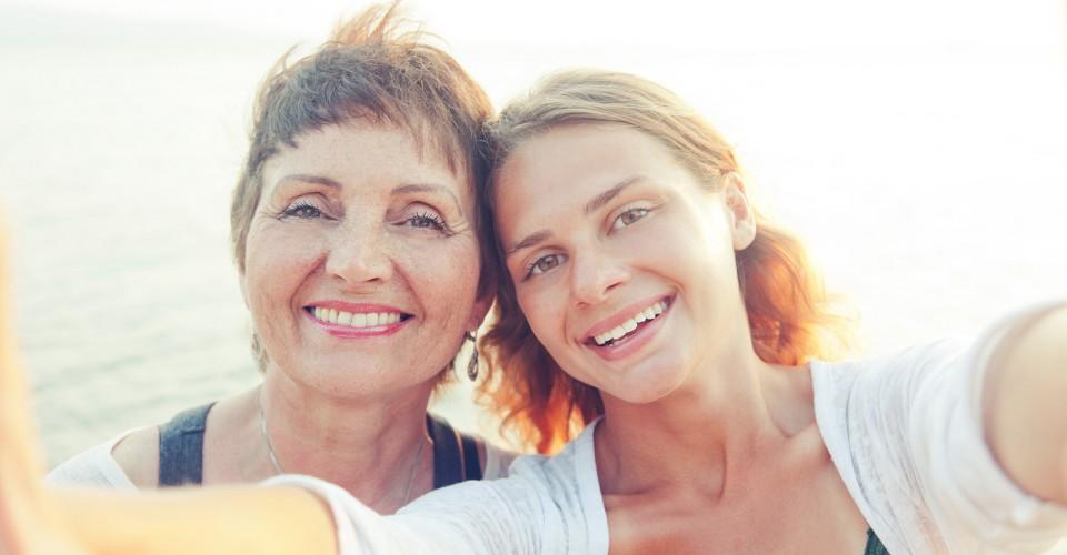 Kaksi naista katsoo suoraan kameraan iloisina päät toisiinsa nojaten. Kuva sivustolla Ilman syöpää.
