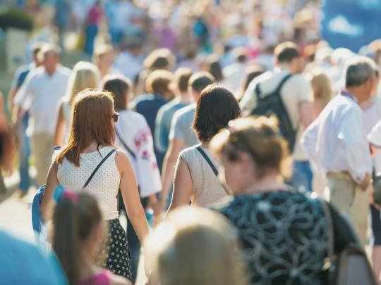 Kuva ihmisjoukosta kävelemässä aurinkoisella kadulla. Kuva sivustolla Ilman syöpää.