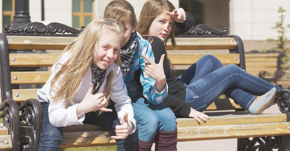Kuvassa nuoria tyttöjä istumassa penkillä. Kuva sivustolla Ilman syöpää.