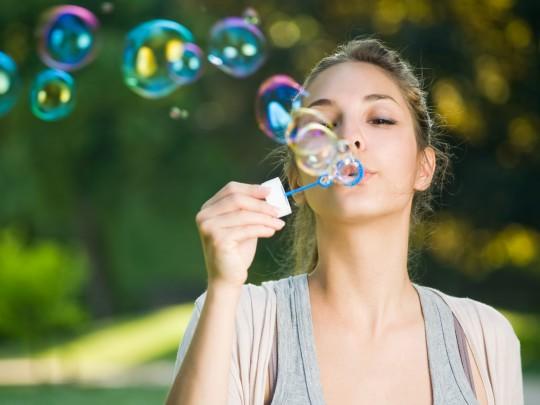 Nuori nainen puhaltaa puistossa saippuakuplia. Kuva sivulla 5 faktaa nikotiinista, sivustolla Ilman syöpää