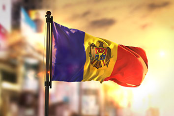 Moldova flag against city blurred background at sunrise backlight