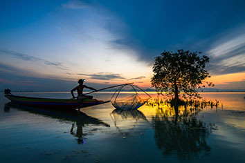 Fisherman on boat catching fish with sunrise
