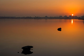 Rocks with reflections on calm water and beautiful sunrise over colorful sky with silhouette background, bahrain