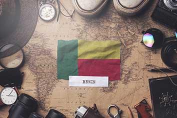 Benin flag between traveler's accessories on old vintage map