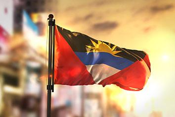 Antigua and barbuda flag against city blurred background at sunrise backlight