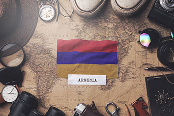 Armenia flag between traveler's accessories on old vintage map