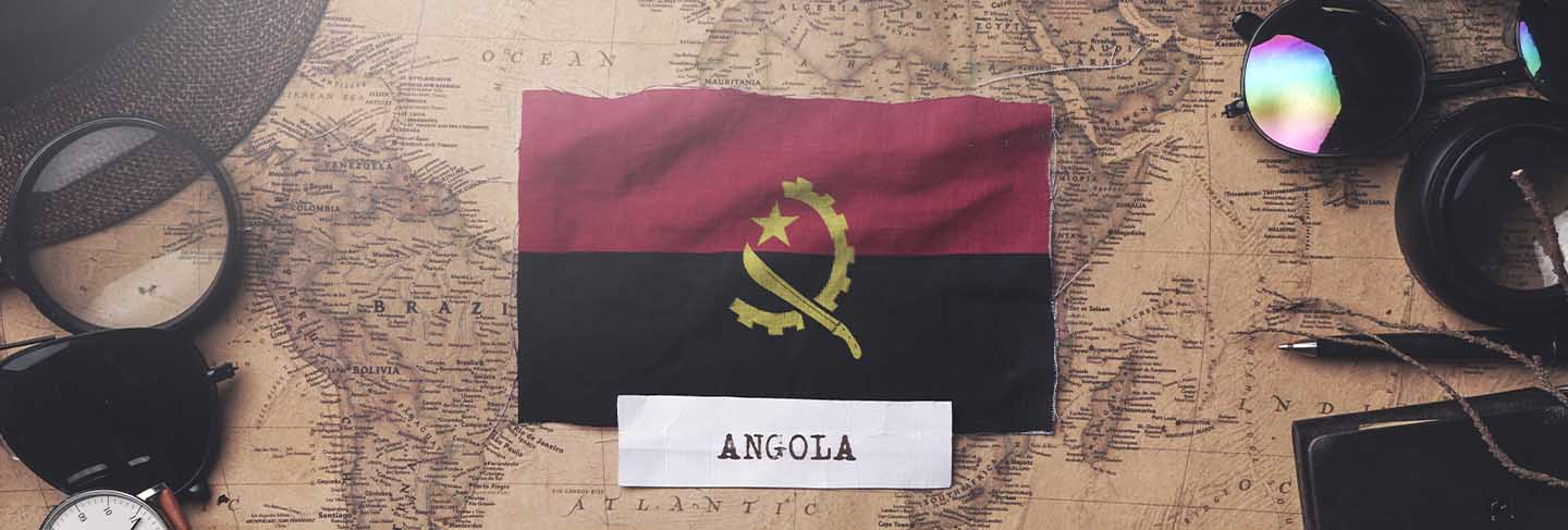 Angola flag between traveler's accessories on old vintage map