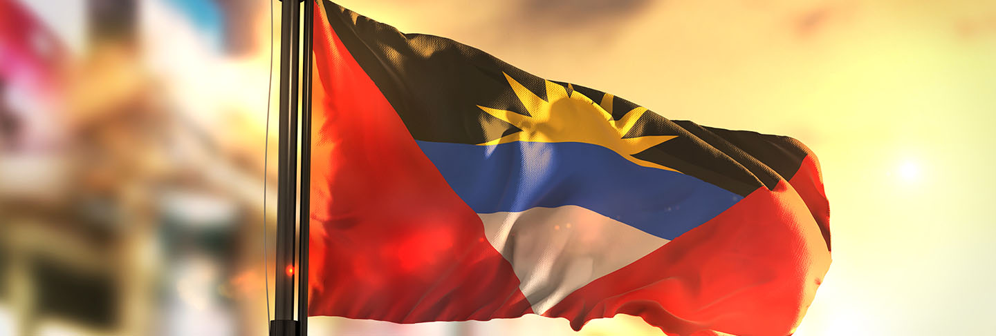 Antigua and barbuda flag against city blurred background at sunrise backlight