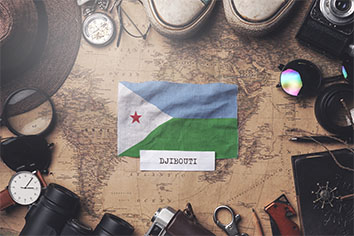 Djibouti flag between traveler's accessories on old vintage map