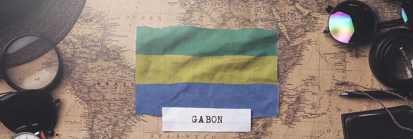 Gabon flag between traveler's accessories on old vintage map