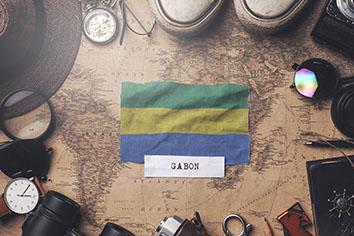 Gabon flag between traveler's accessories on old vintage map