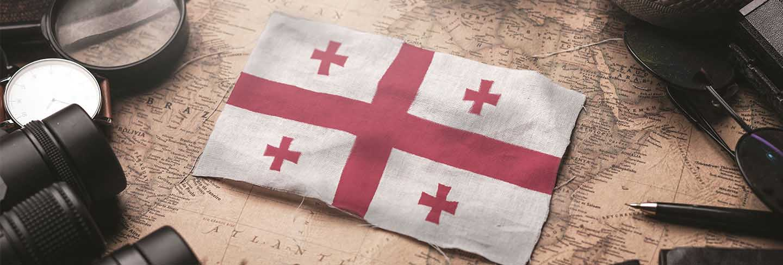 Georgia flag between traveler's accessories on old vintage map