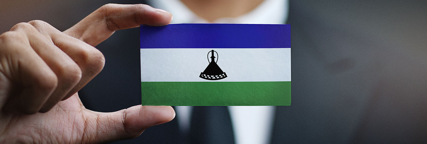 Businessman holding card of lesotho flag