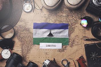 Lesotho flag between traveler's accessories on old vintage map