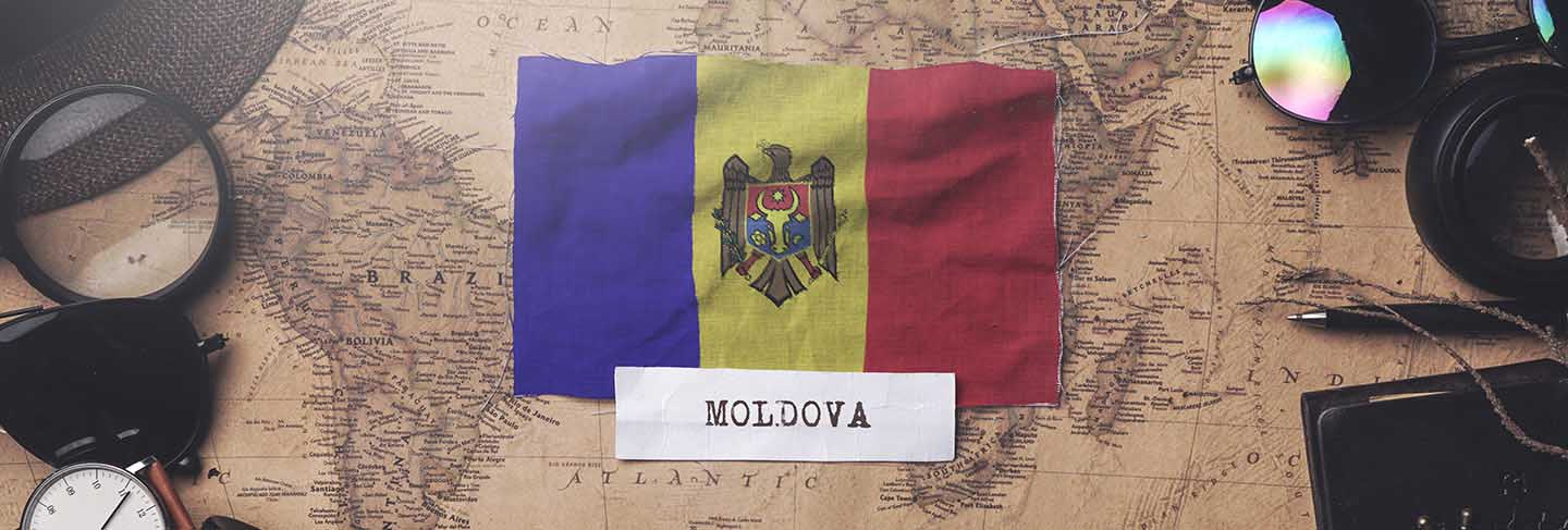 Moldova flag between traveler's accessories on old vintage map