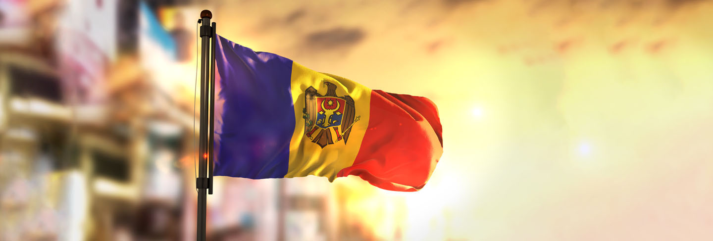 Moldova flag against city blurred background at sunrise backlight