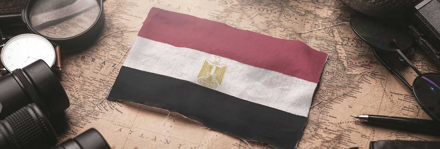 Egypt flag between traveler's accessories on old vintage map. tourist destination concept