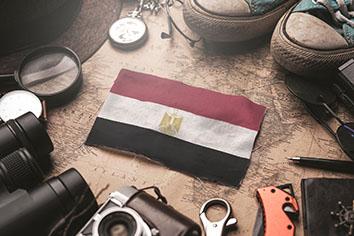 Egypt flag between traveler's accessories on old vintage map. tourist destination concept