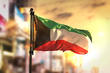 Kuwait flag against city blurred background at sunrise backlight