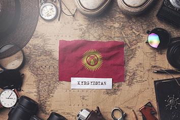 Kyrgyzstan flag between traveler's accessories on old vintage map.