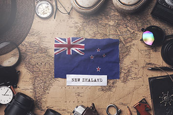 New zealand flag between traveler's accessories on old vintage map